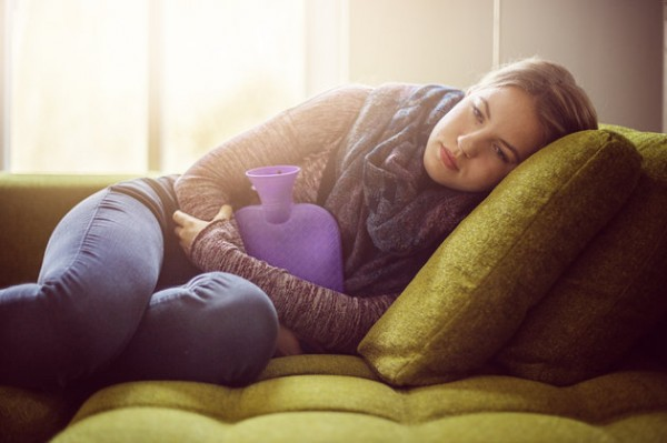 Teenage girl with hot water bottle on sofa