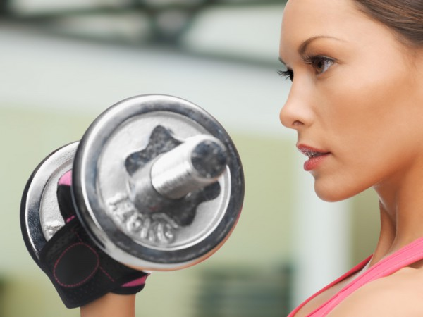 concentrated woman with dumbbells in gym