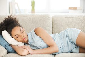 Beautiful woman sleeping. Attractive young African woman sleeping while lying on sofa at home