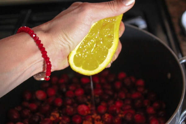 Squeezing an orange over cranberries
